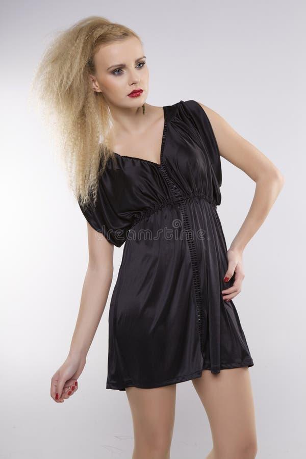 Молодая милая женщина с красивыми светлыми волосами в черном платье стоковое фото rf