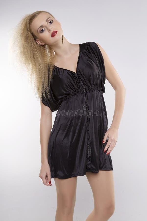Молодая милая женщина с красивыми светлыми волосами в черном платье стоковое изображение rf