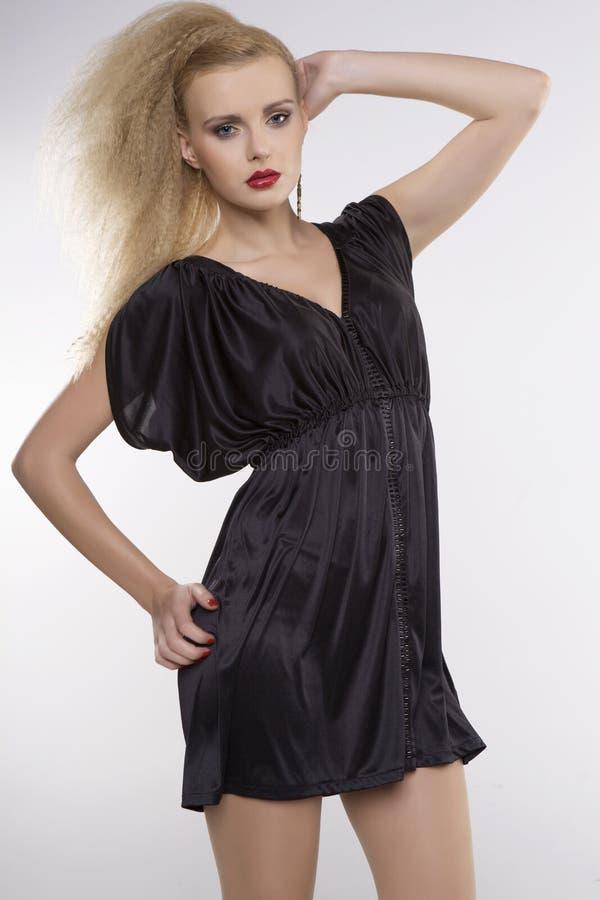 Молодая милая женщина с красивыми светлыми волосами в черном платье стоковое фото