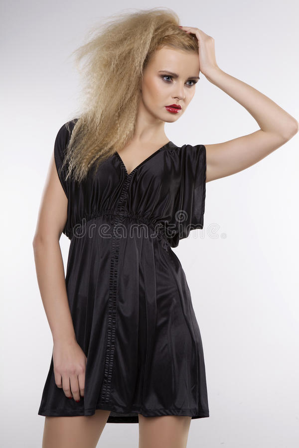 Молодая милая женщина с красивыми светлыми волосами в черном платье стоковое изображение
