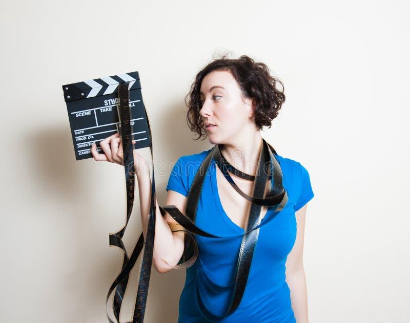 Молодая милая женщина с filmstrip вокруг шеи держит clappe кино стоковые изображения rf