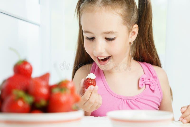Молодая милая усмехаясь европейская маленькая девочка ест зрелую клубнику jucy с сметаной и держит белую плиту много стоковые изображения rf