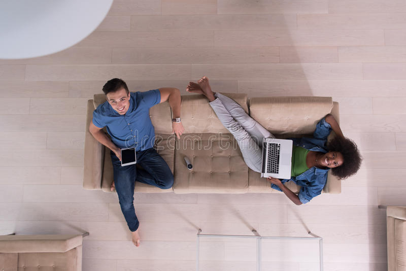 Молодая многонациональная пара ослабляет в взгляд сверху живущей комнаты стоковые изображения rf