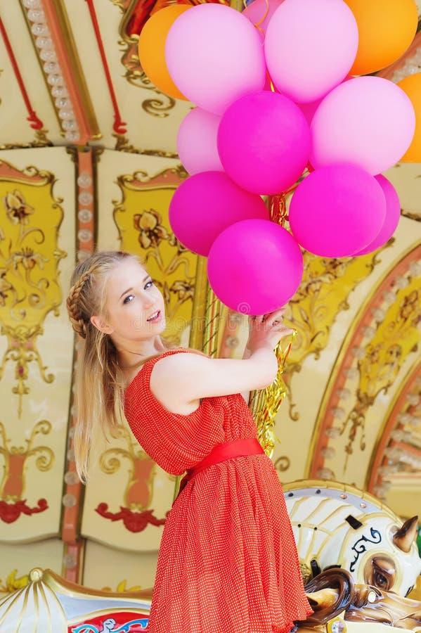 Молодая модельная женщина ехать carousel стоковое изображение