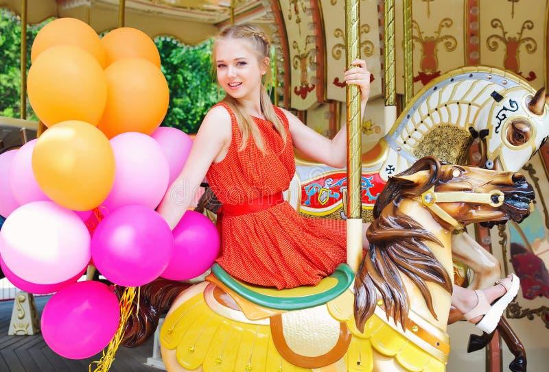 Молодая модельная женщина ехать carousel стоковое фото rf