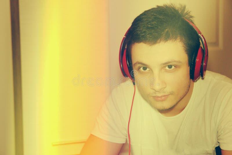 Молодая мужская модель слушая к музыке на камере дома стоковые изображения