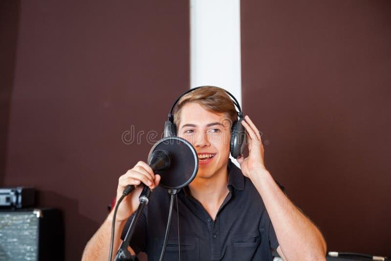Молодая мужская певица выполняя в студии стоковые изображения rf