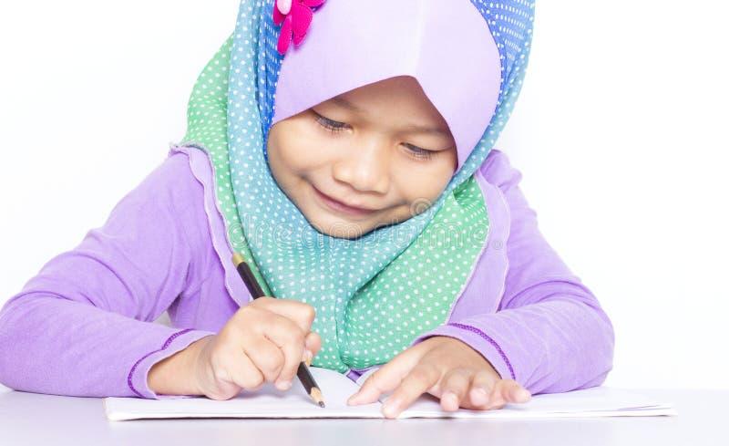 Молодая мусульманская девушка писать книгу на столе стоковое фото rf