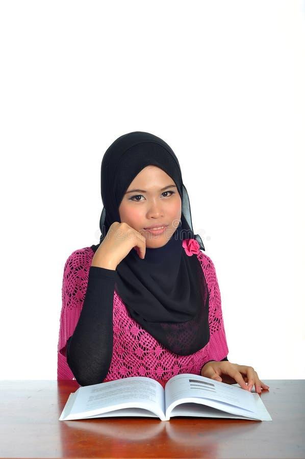 Молодая мусульманская женщина изучая с книгой стоковое изображение rf