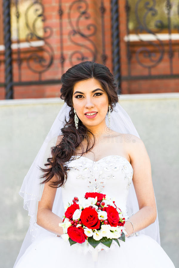 Молодая невеста в платье свадьбы держа букет стоковые фото