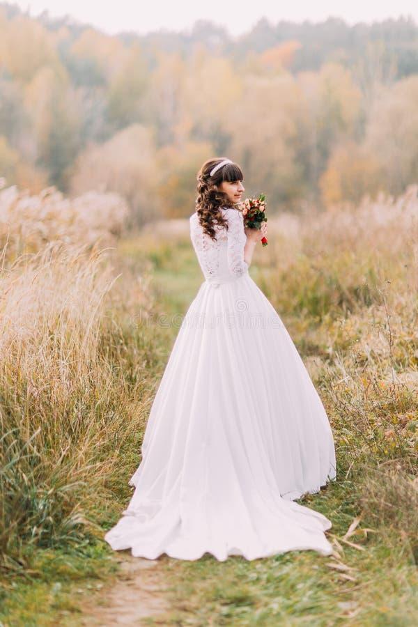 Молодая невеста представляя outdoors Милая очаровательная девушка с Forest Hills на предпосылке стоковое фото