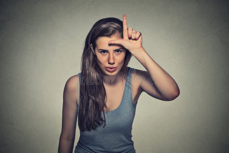 Молодая несчастная женщина давая знак проигравшего на лбе стоковая фотография