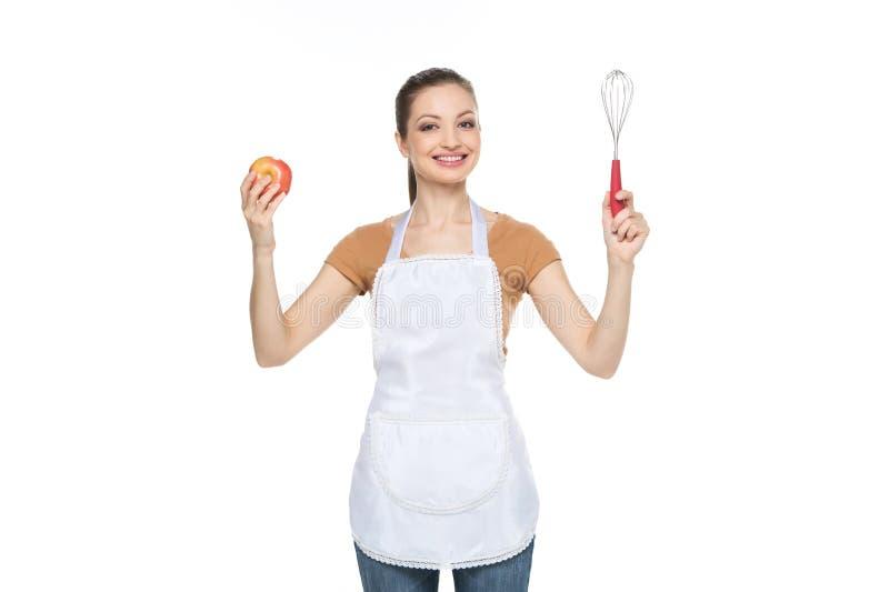 Молодая домохозяйка держа красное яблоко стоковые фото
