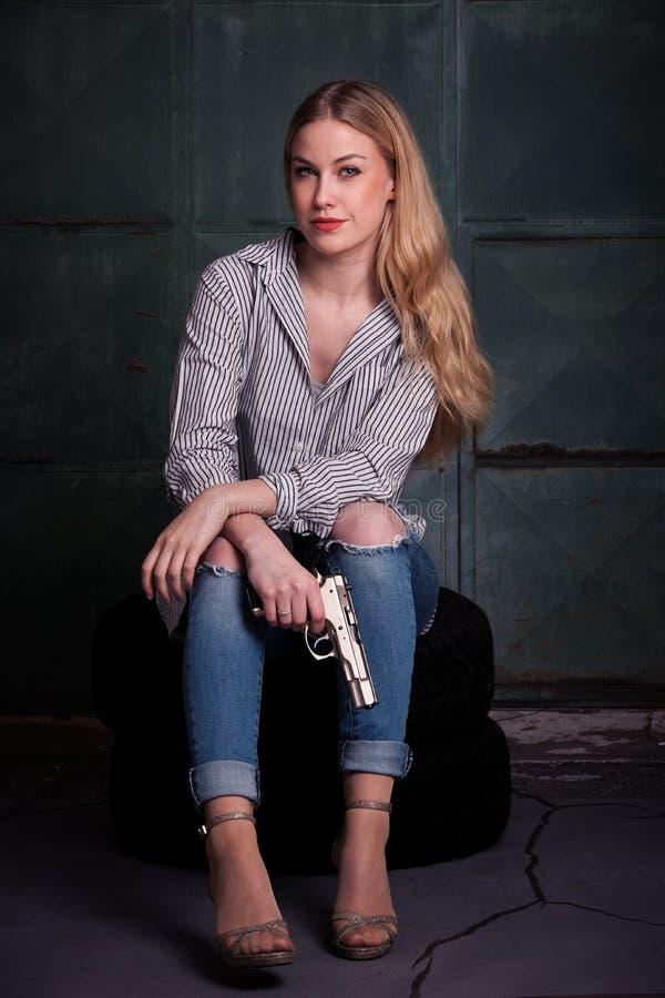 Молодая опасная белокурая женщина с оружием стоковые фотографии rf