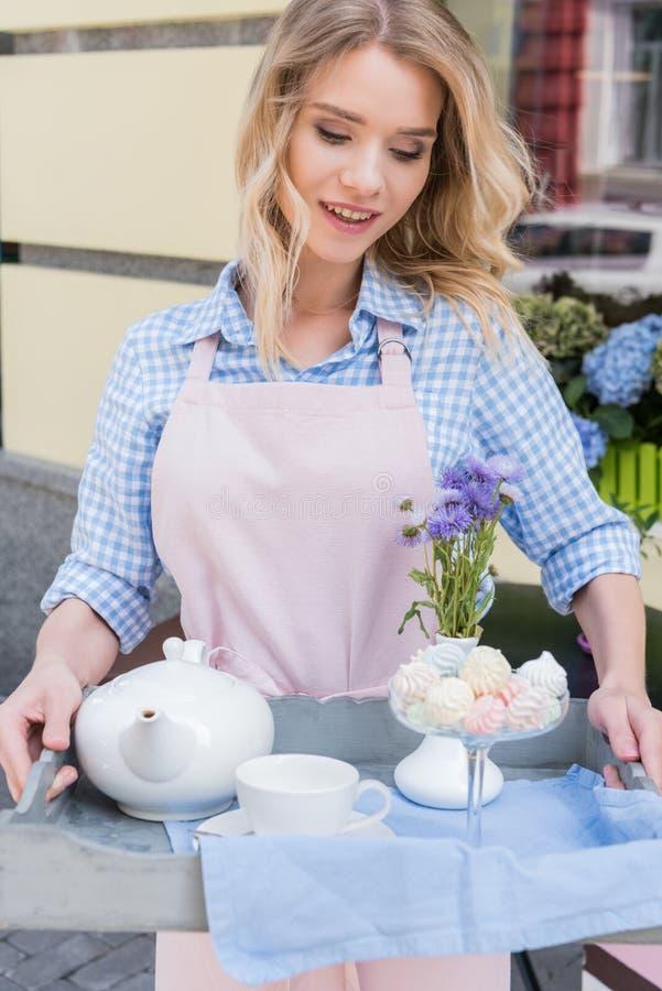 Молодая официантка в рисберме держа поднос с комплектом чая в внешнем кафе стоковая фотография