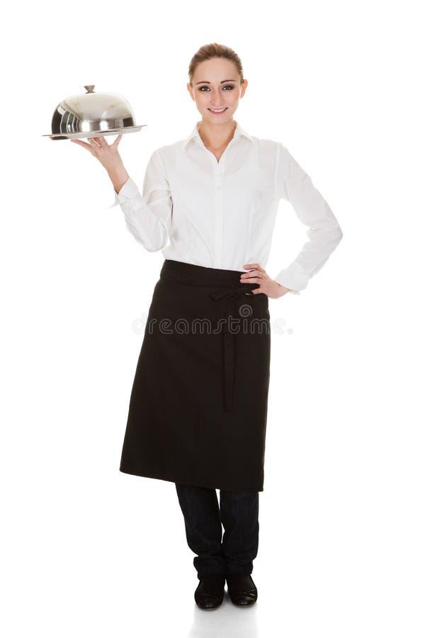 Молодая официантка держа поднос и крышку стоковая фотография rf
