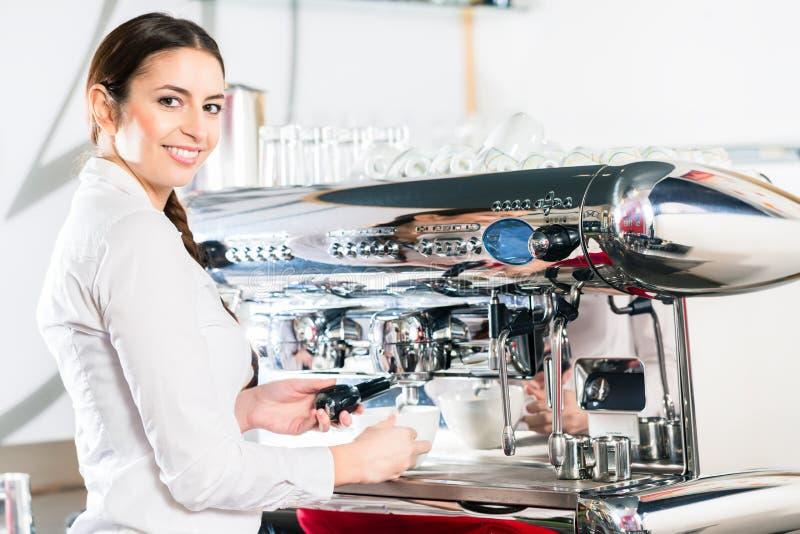 Молодая официантка используя автоматическую машину кофе стоковые фотографии rf