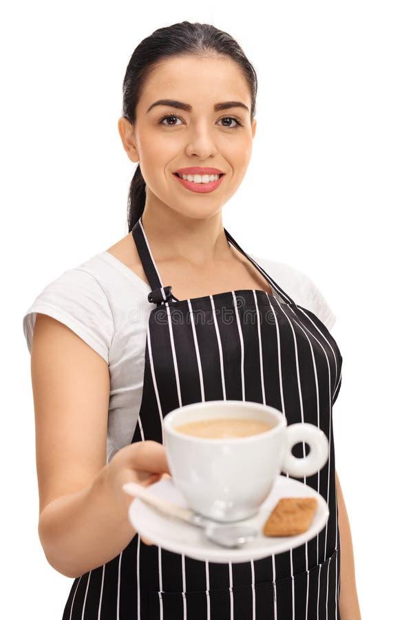 Молодая официантка предлагая чашку кофе стоковое фото rf