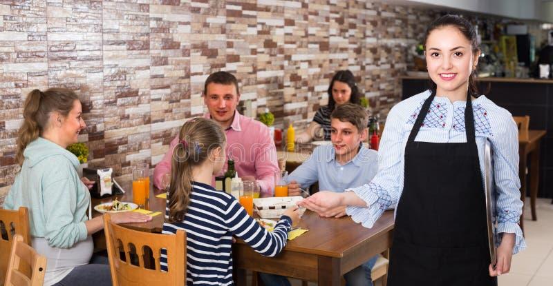 Молодая официантка с меню приглашает стоковое фото rf