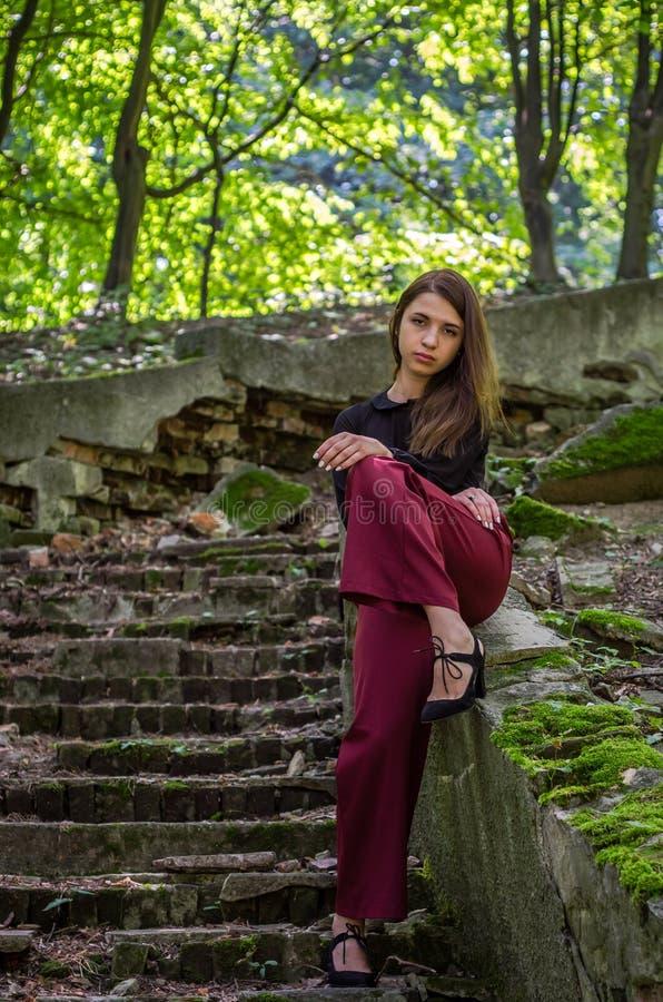 Молодая очаровательная девушка подростка при длинные темные волосы грациозно походка разрушенные старой лестницей шаги в парк i S стоковые фотографии rf