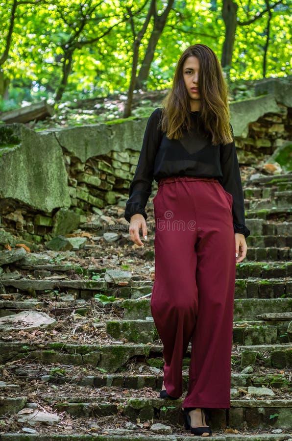 Молодая очаровательная девушка подростка при длинные темные волосы грациозно походка разрушенные старой лестницей шаги в парк i S стоковая фотография rf