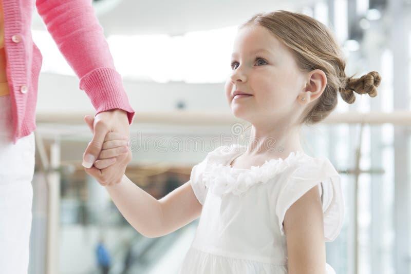 Молодая дочь держа руку матерей стоковые фото