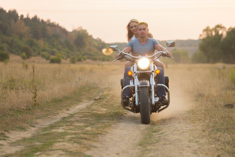 Молодая пара в поле рядом с мотоциклом стоковые изображения
