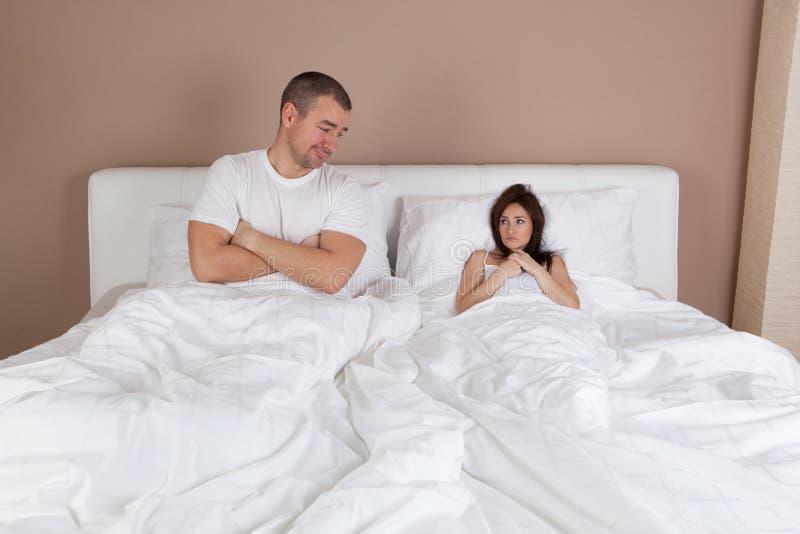 Молодая пара лежа в кровати и женщине очень мала стоковое изображение rf