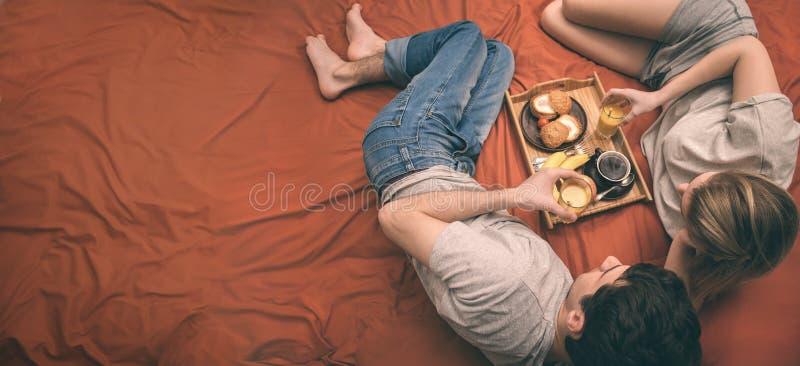 Молодая пара лежит в кровати стоковое изображение