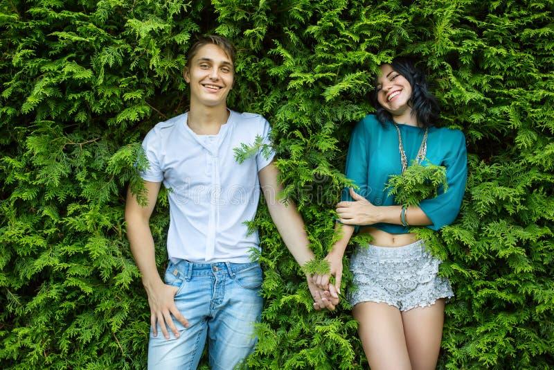 Молодая пара держа руки на задней части яркая ая-зелен листва стоковая фотография rf