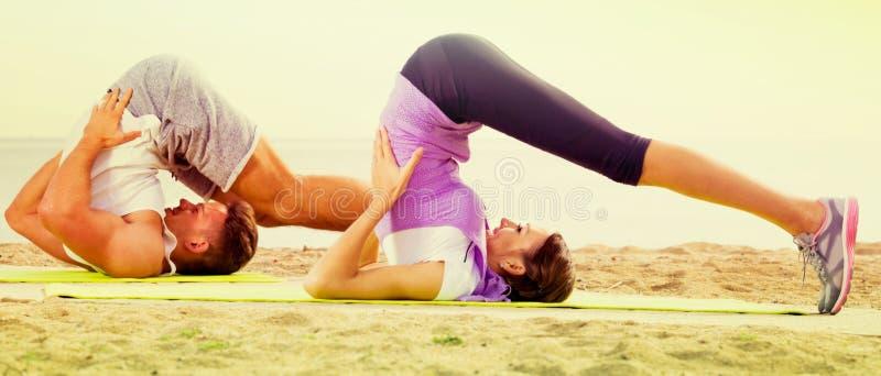Молодая пара делая йогу представляет сидеть на солнечном пляже стоковые изображения