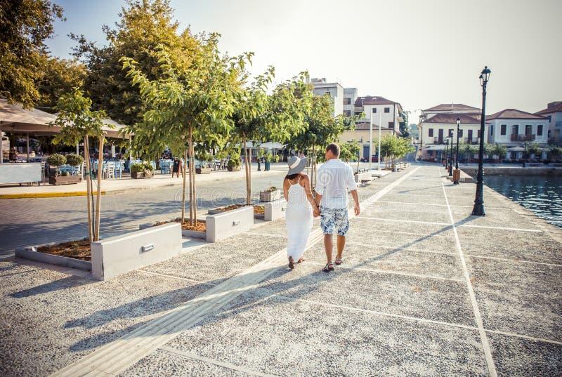 Молодая пара идет держащ девушку в длинном платье стоковые фотографии rf