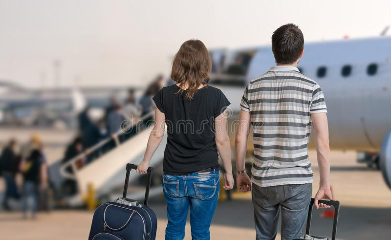 Молодая пара путешествует на каникулах Человек и женщина с багажем в авиапорте стоковые изображения