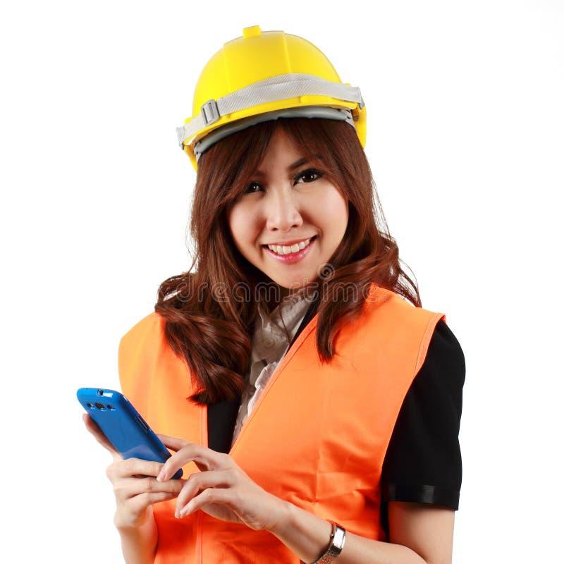 Молодая привлекательная азиатская женщина инженера стоя используя передвижной phon стоковое изображение rf