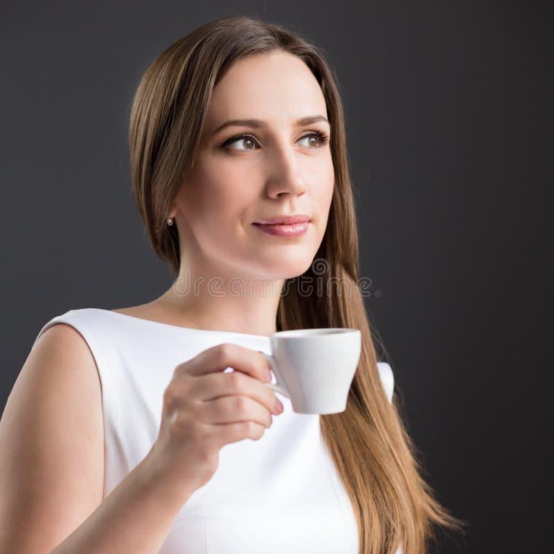 Молодая привлекательная бизнес-леди имея кофейную чашку стоковое фото
