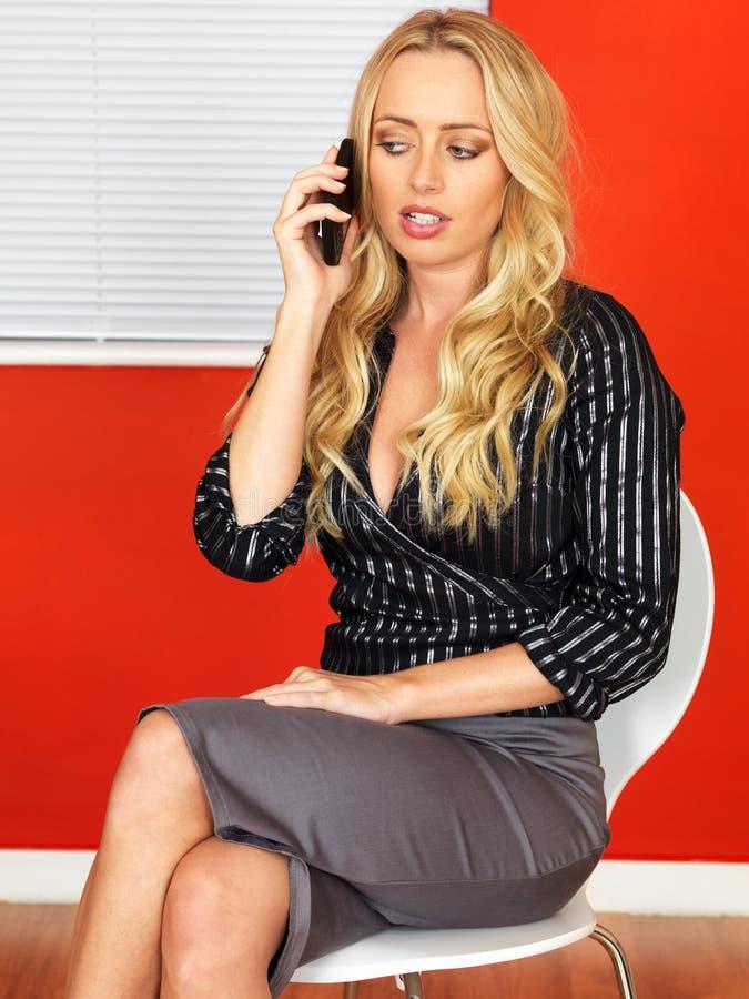 Молодая привлекательная бизнес-леди используя мобильный телефон стоковое изображение
