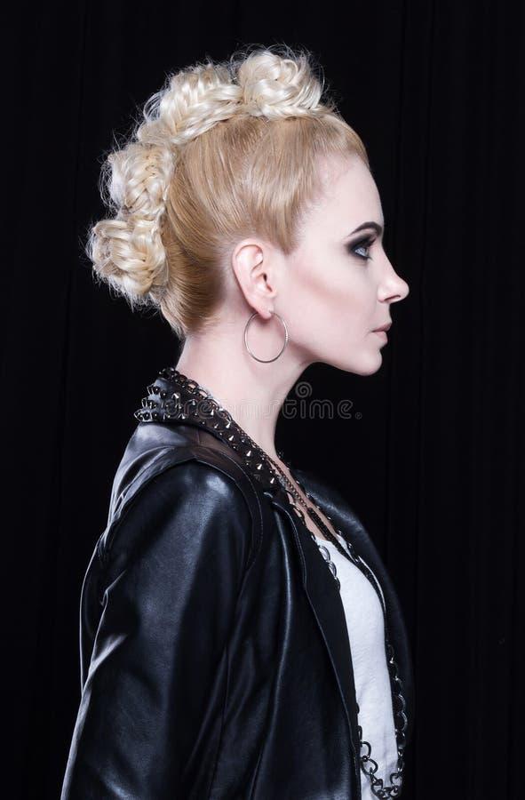 Молодая привлекательная блондинка в кожаной куртке Она воинственно настроена, она имеет творческий mohawk стоковое изображение rf
