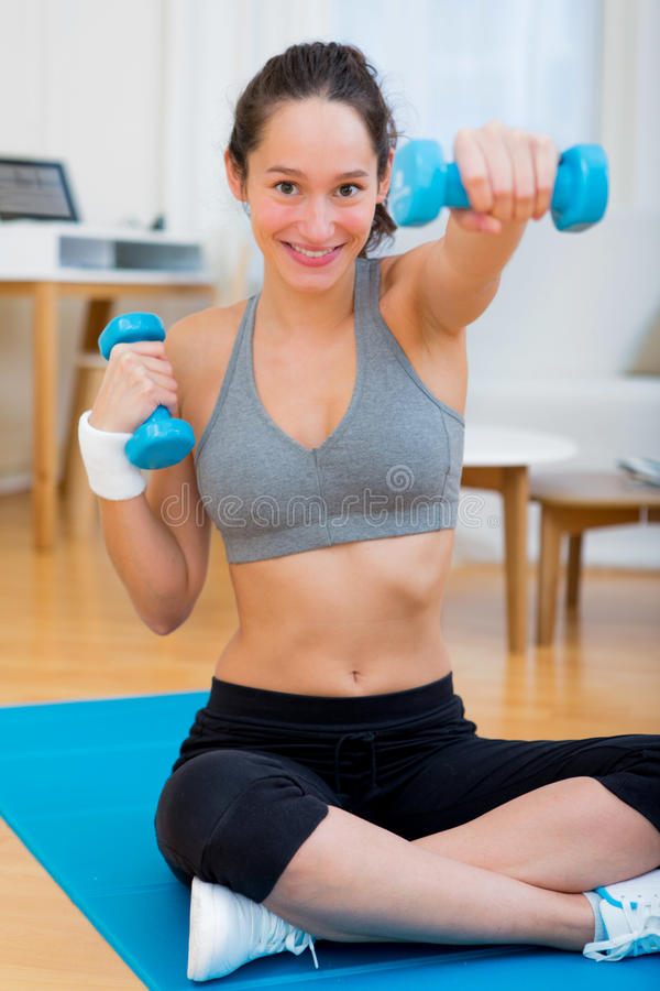 Молодая привлекательная девушка делая тренировку дома стоковое фото rf