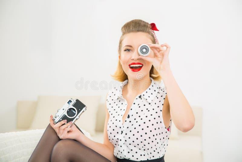 Молодая привлекательная девушка играя с частями камеры стоковое изображение rf