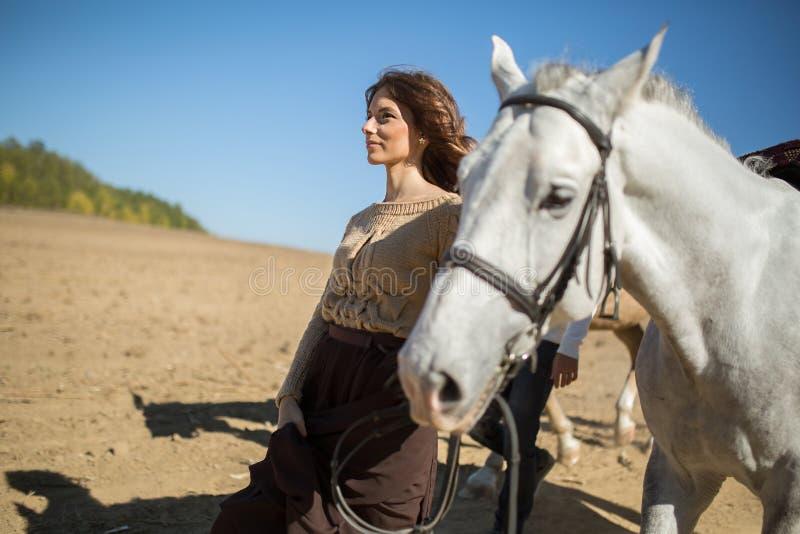 Молодая привлекательная девушка идет с его лошадью стоковые фото