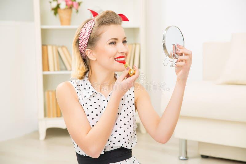 Молодая привлекательная девушка кладя губную помаду дальше стоковое изображение rf