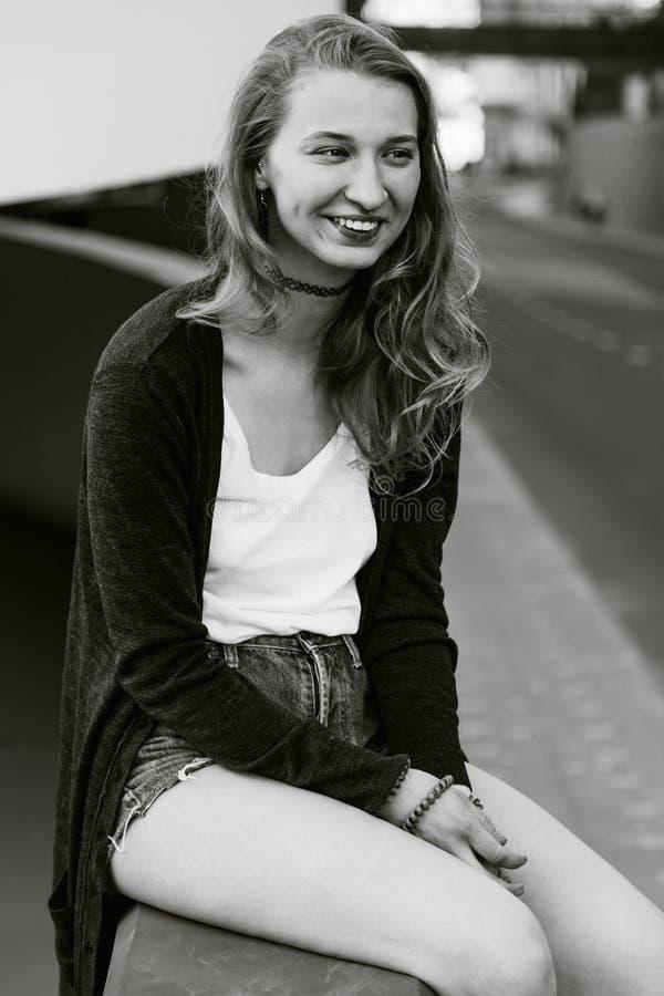 Молодая привлекательная девушка сидит снаружи стоковая фотография
