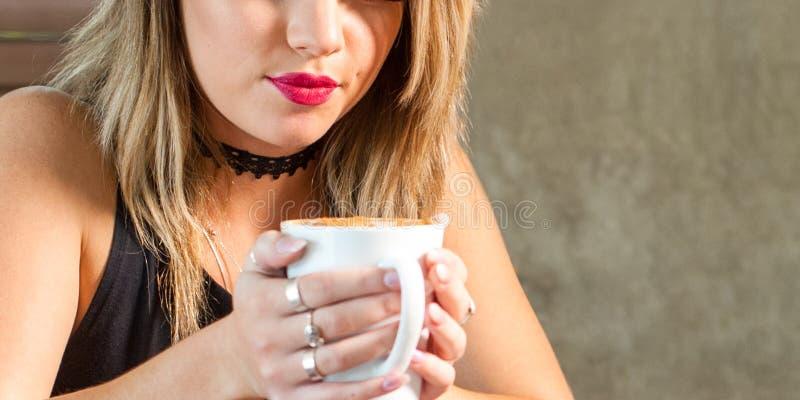 Молодая привлекательная женщина выпивая очень вкусный горячий напиток стоковое изображение rf