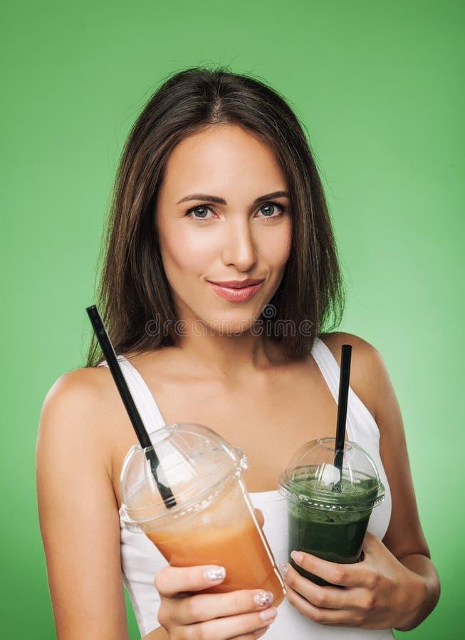 Молодая привлекательная женщина держа smoothie стоковое изображение rf