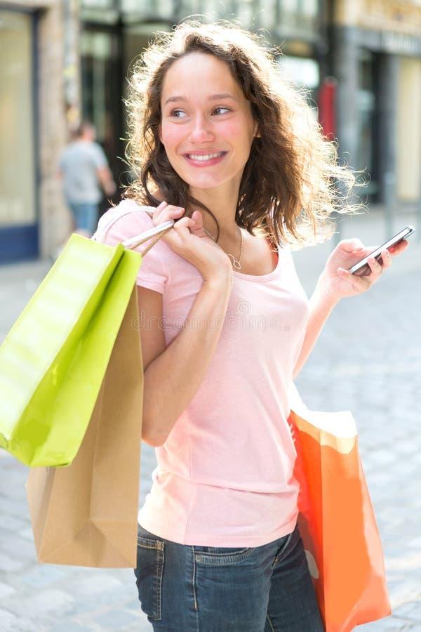 Молодая привлекательная женщина используя чернь во время покупок стоковое фото rf