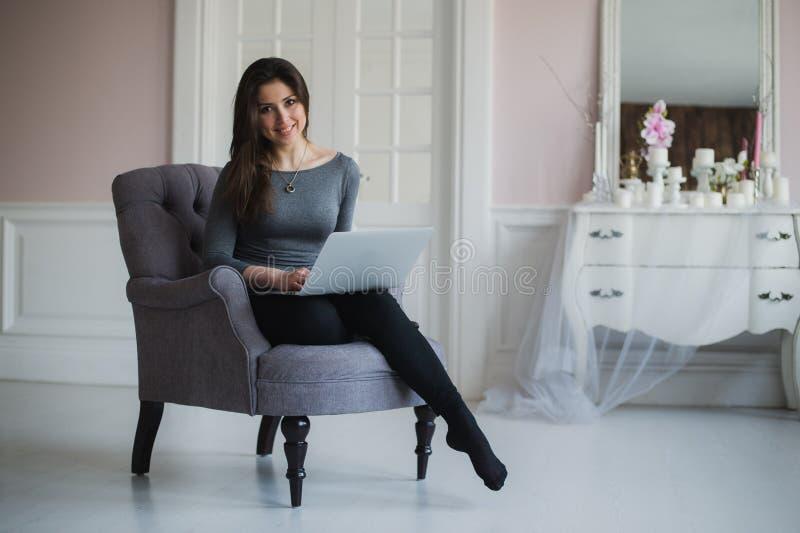 Молодая привлекательная женщина дома, работающ с компьтер-книжкой, свободные онлайн классы для интереса, сидящий дома начинать ма стоковая фотография
