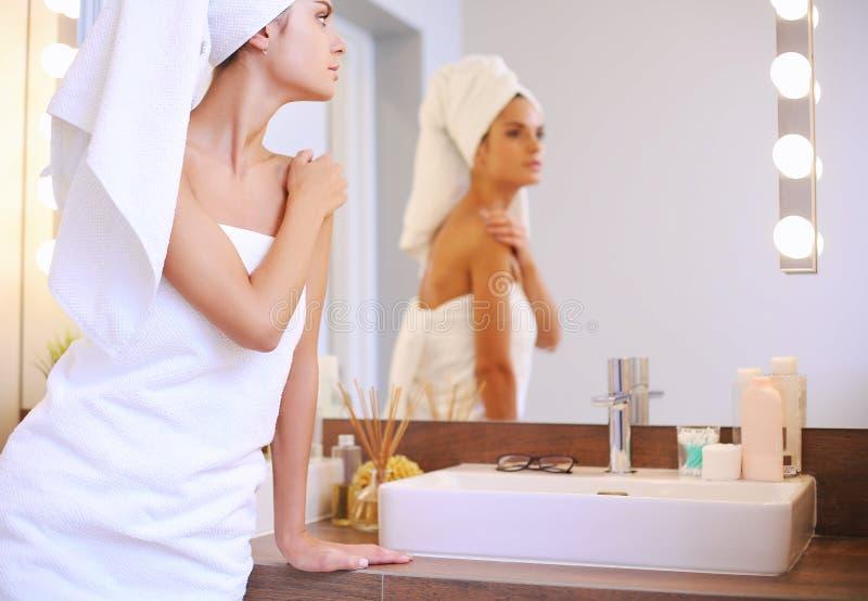 Молодая привлекательная женщина стоя перед зеркалом ванной комнаты стоковое фото rf