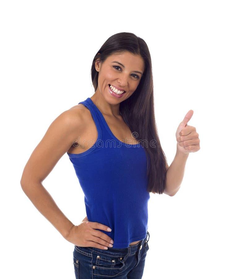Молодая привлекательная испанская женщина в вскользь верхней части и джинсы усмехаясь счастливый и жизнерадостный давать thumb вв стоковые фотографии rf