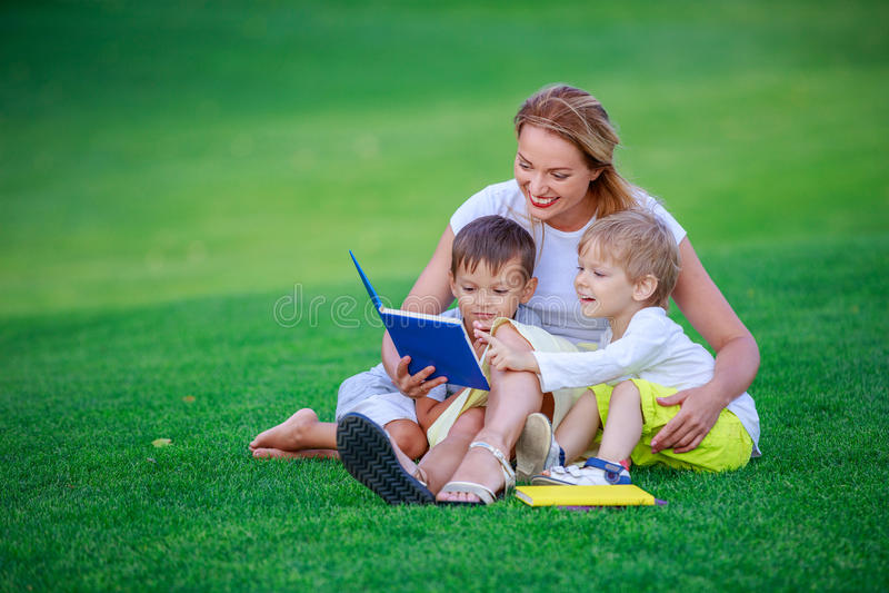 Молодая привлекательная мать читает книгу рассказа к ее 2 малым детям стоковая фотография