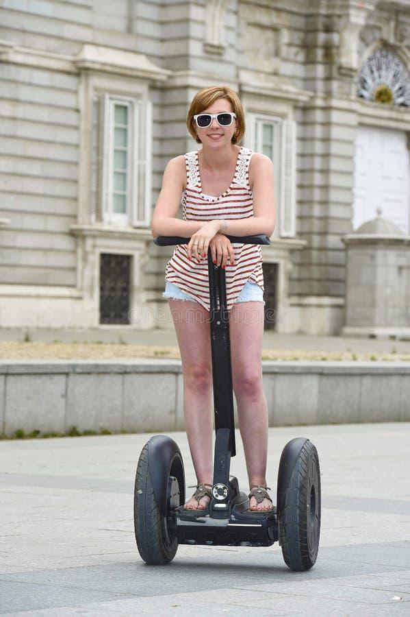 Молодая привлекательная туристская женщина в путешествии города шортов ехать счастливое электрическое segway в Испании стоковая фотография rf